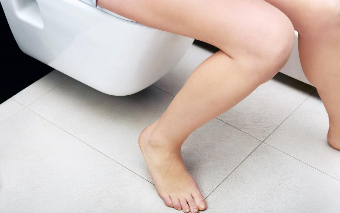 a woman on the toilet experiencing constipation