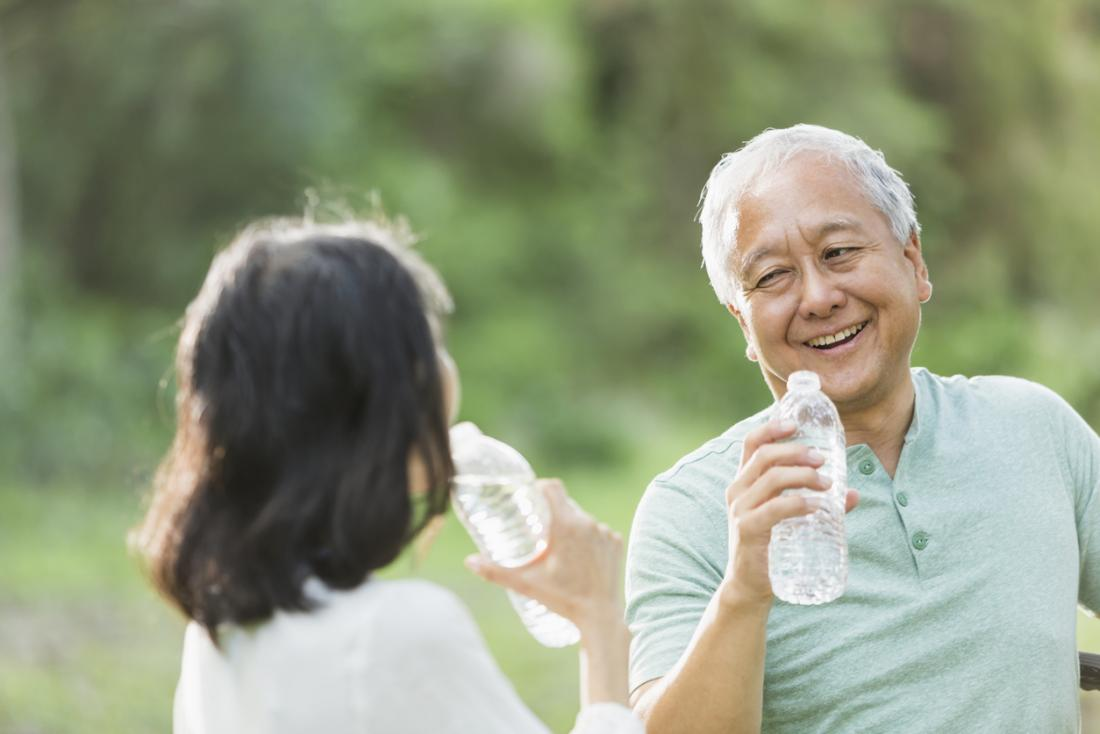 Older Asian adult drinking water