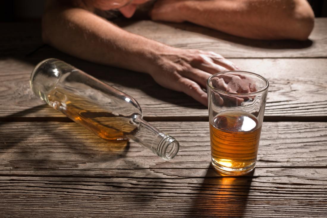 Alcoholic slumped next to glass of alcohol.