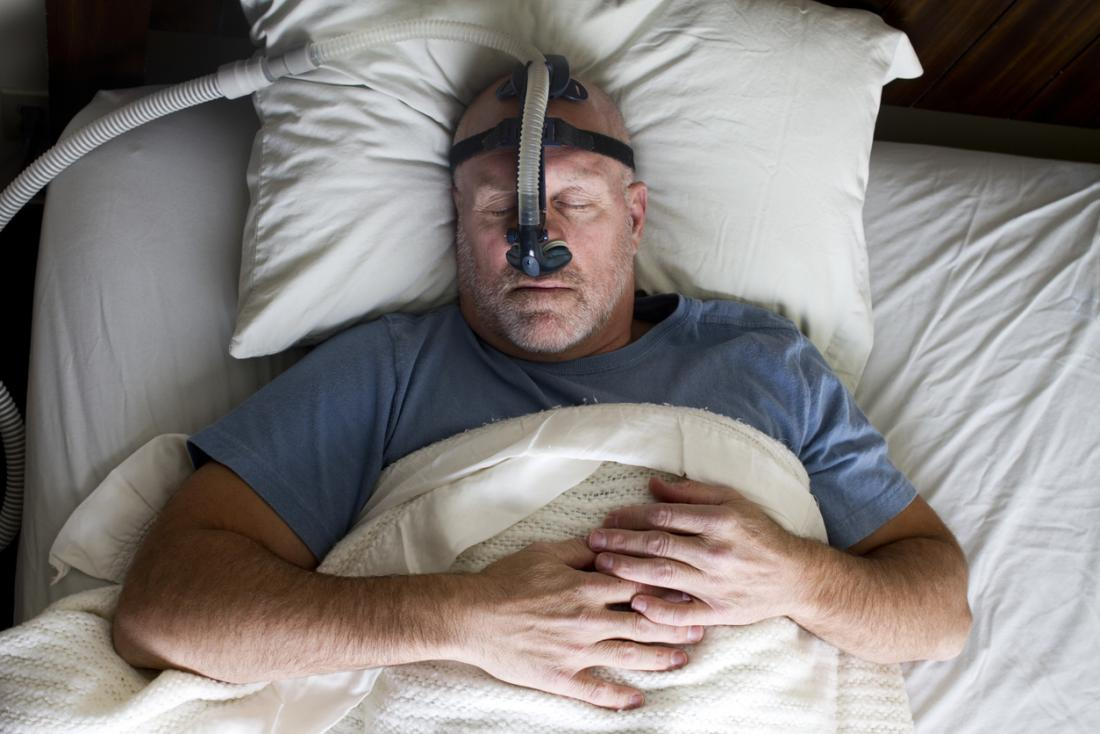 Man asleep with CPAP therapy mask on.