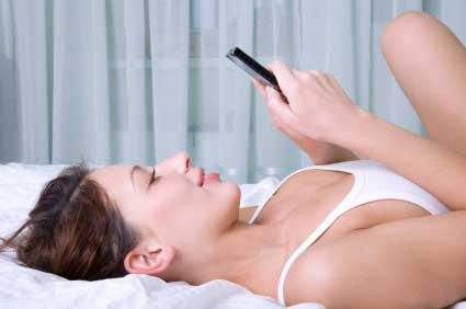 Teenager texting on bed