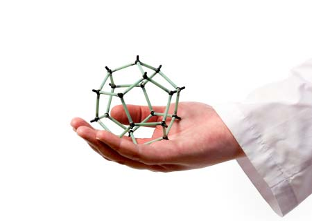 Scientist's hand holding molecular model of graphite sphere