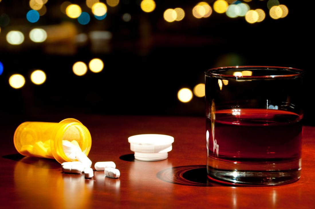 An open bottle of pills next to a glass of alcohol.