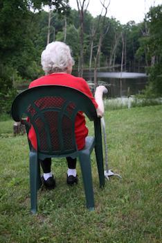 Older lady sitting by a lake