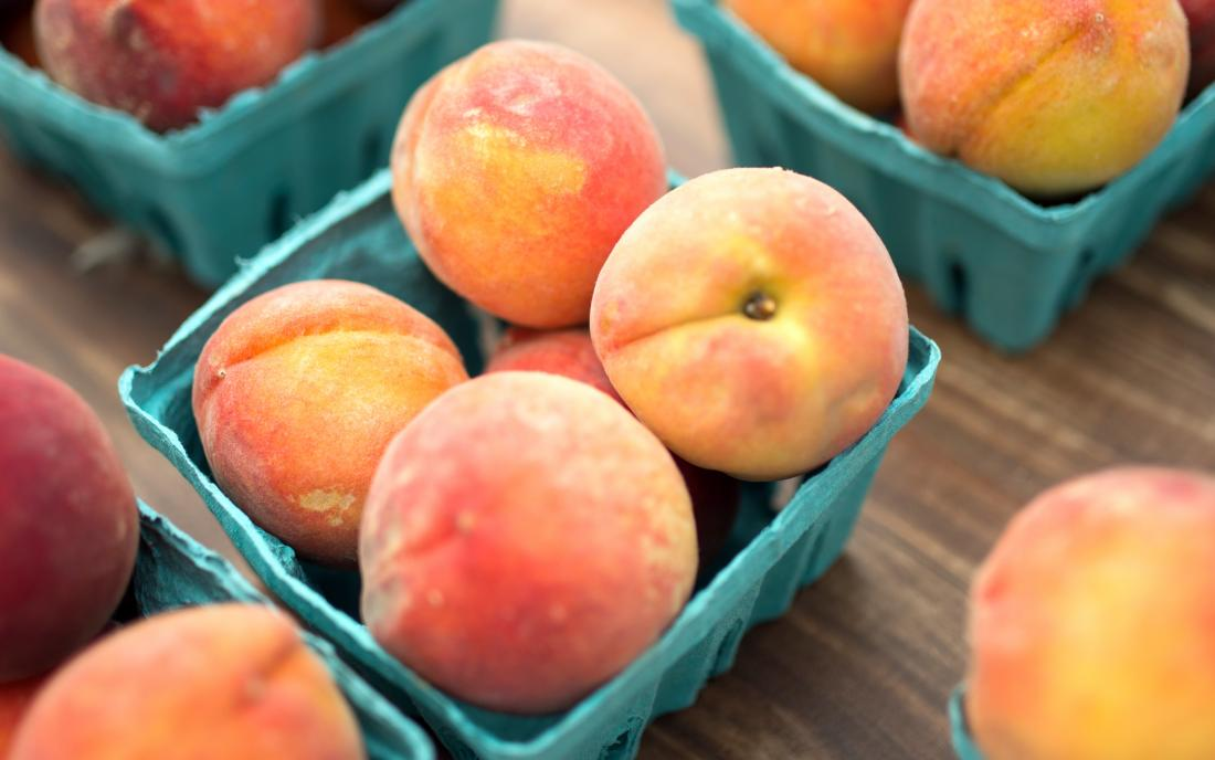 peaches in baskets on a wooden table