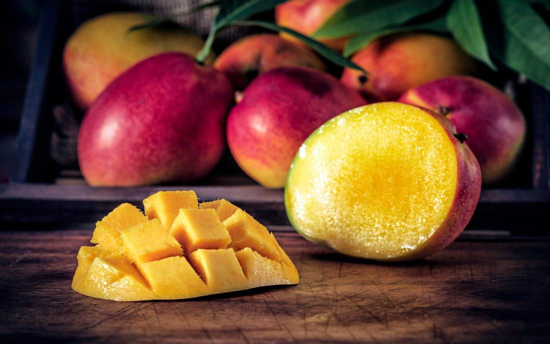 sliced ripe mangoes in rustic kitchen