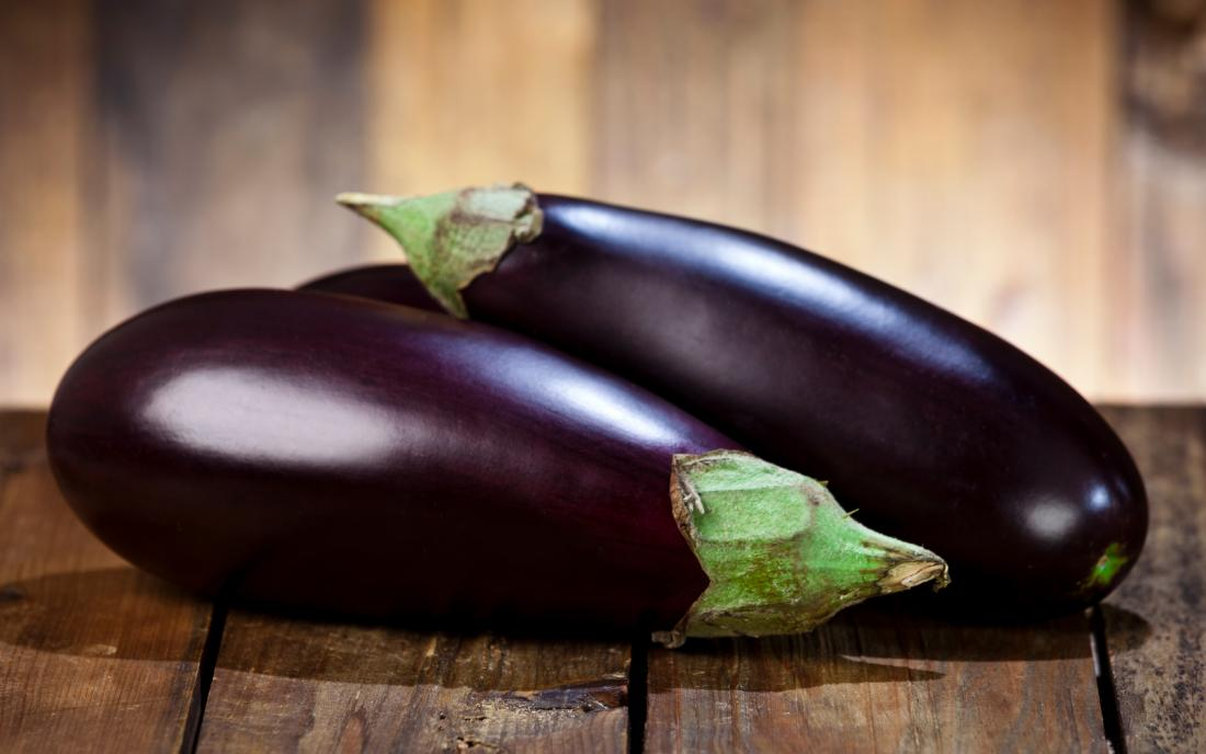 two eggplants on a wooden table.