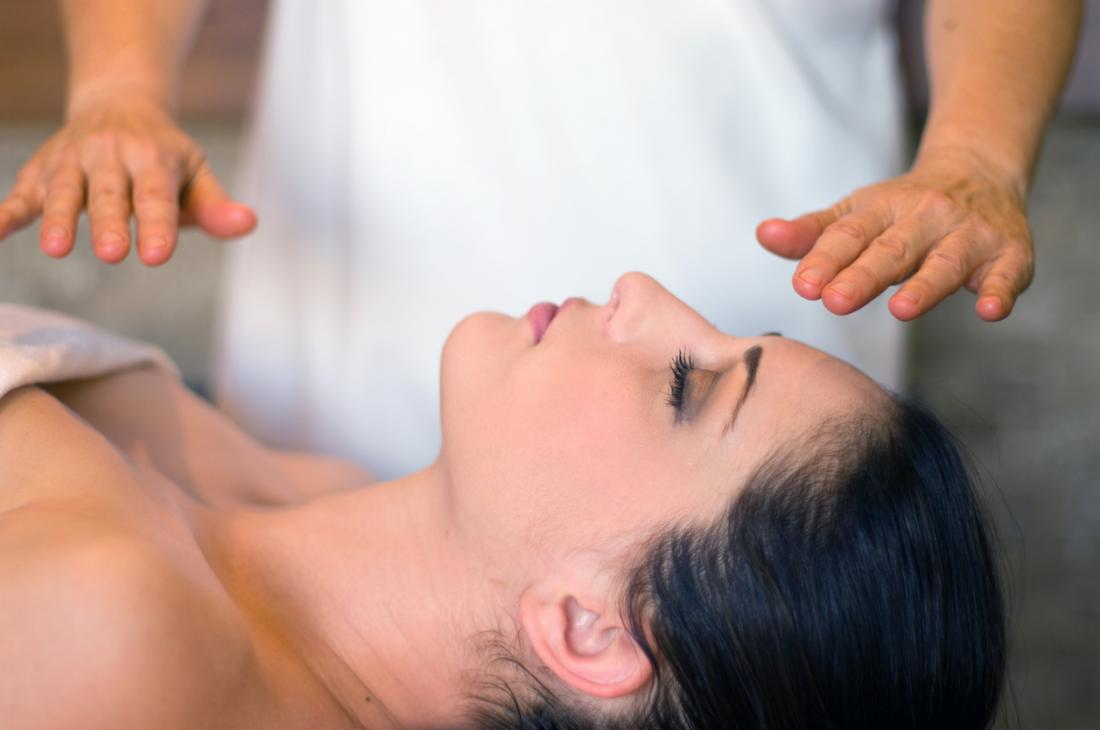 In Reiki, the practitioner transfers energy by placing their hands over or on the patient.
