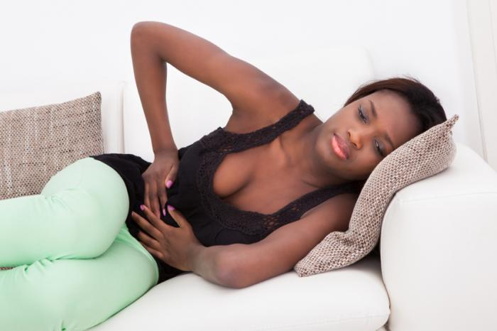 A woman is lying down with abdominal pain.