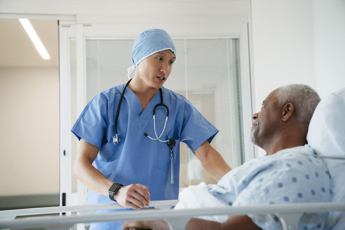 surgeon speaking to patient in hospital bed