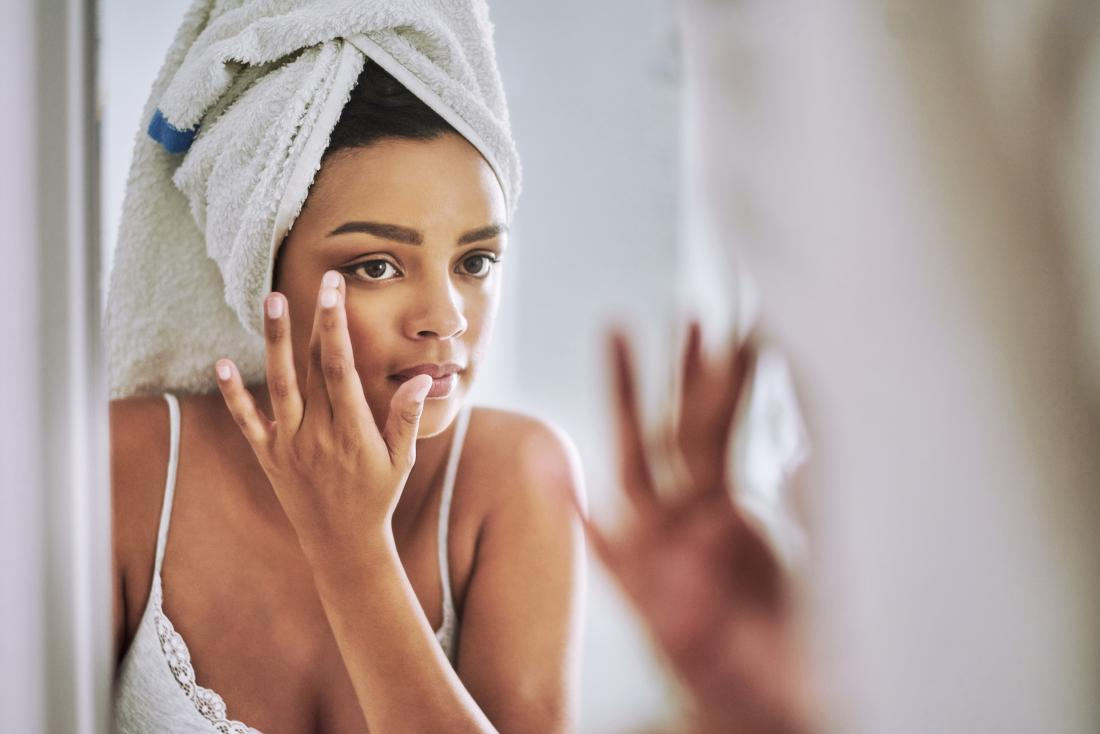young woman looking at eyelid in the mirror