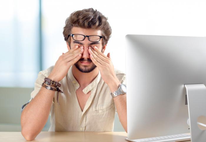 Man rubs eyes at work