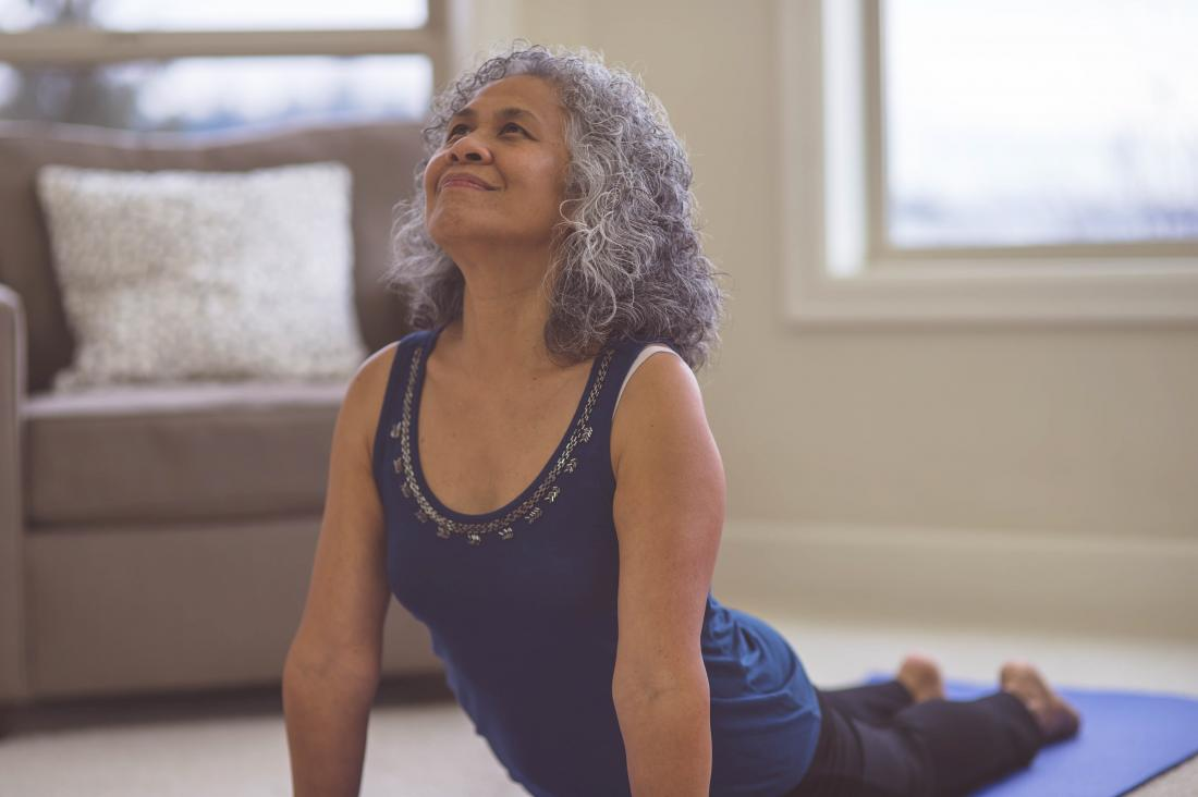 older woman lifts her torso off the ground in a yoga pose at home