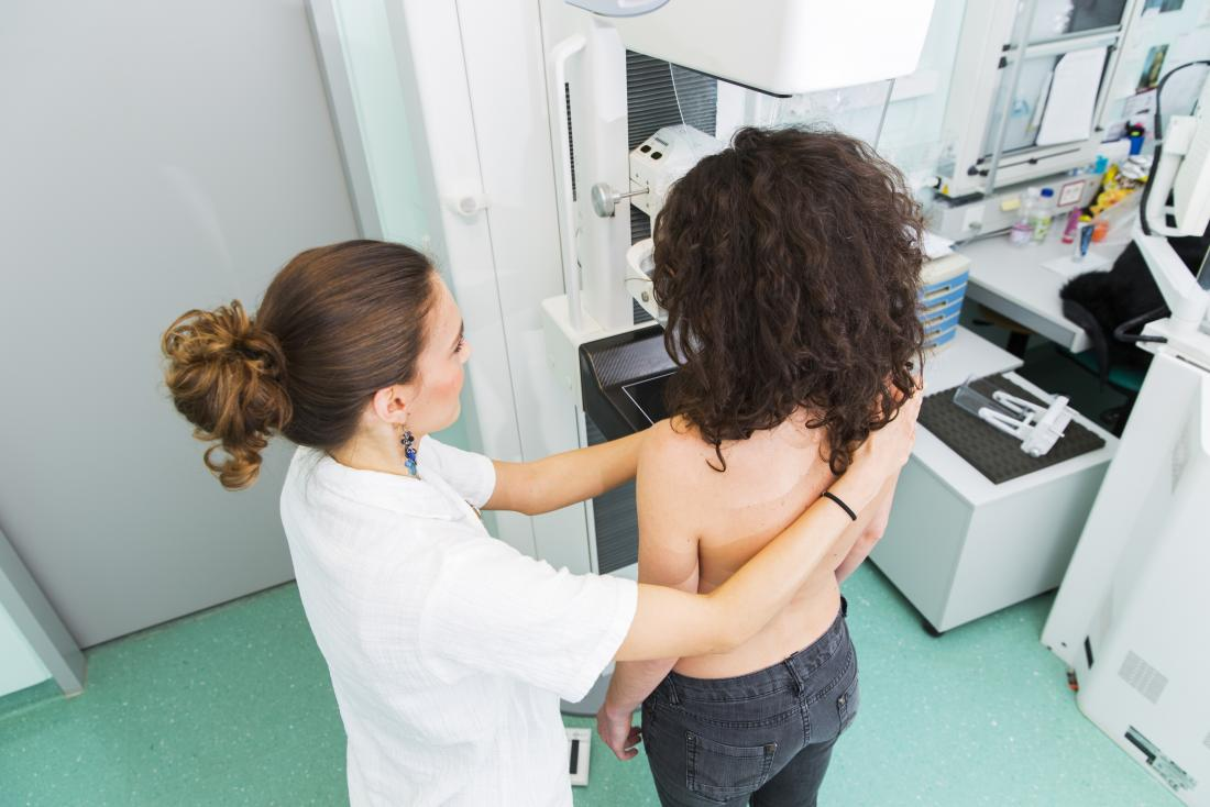 a Nurse with young women having a mammography to check for scattered fibroglandular breast tissue