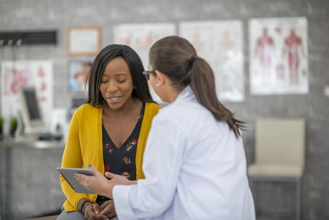 a doctor showing a patient information on an ipad