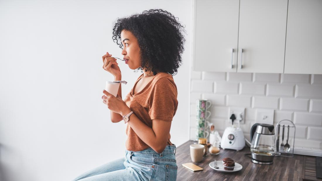 a woman sat in her kitchen eating yogurt as a Natural remedies for managing her ulcerative colitis