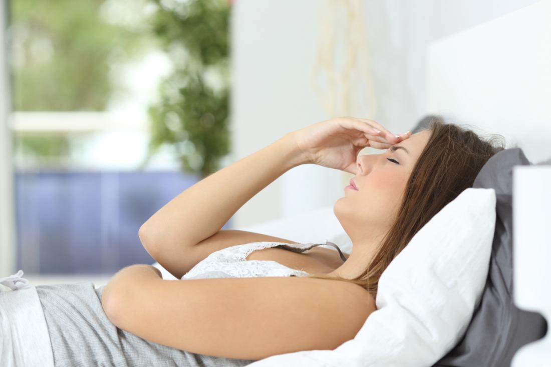 woman lies down with headache