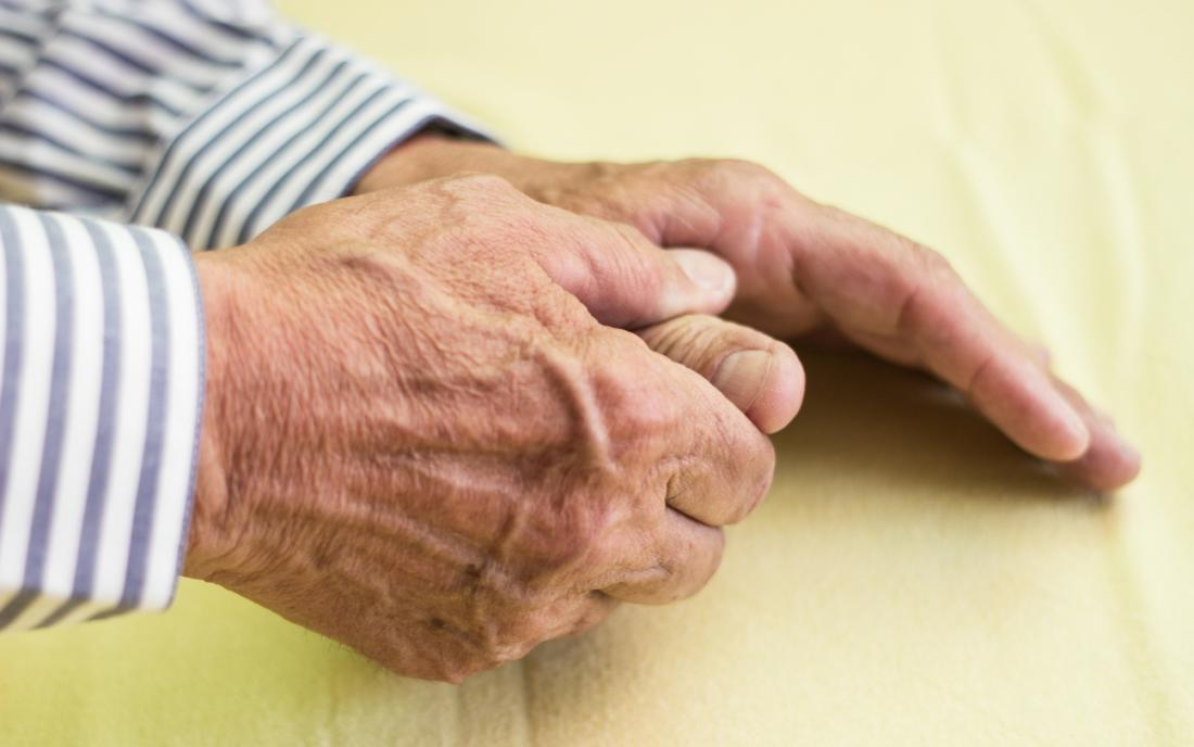 Elderly man's hand, one hand holding the thumb of the other due to arthritis pain.