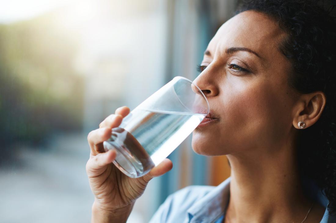 Người phụ nữ uống nước từ ly, giữ nước.