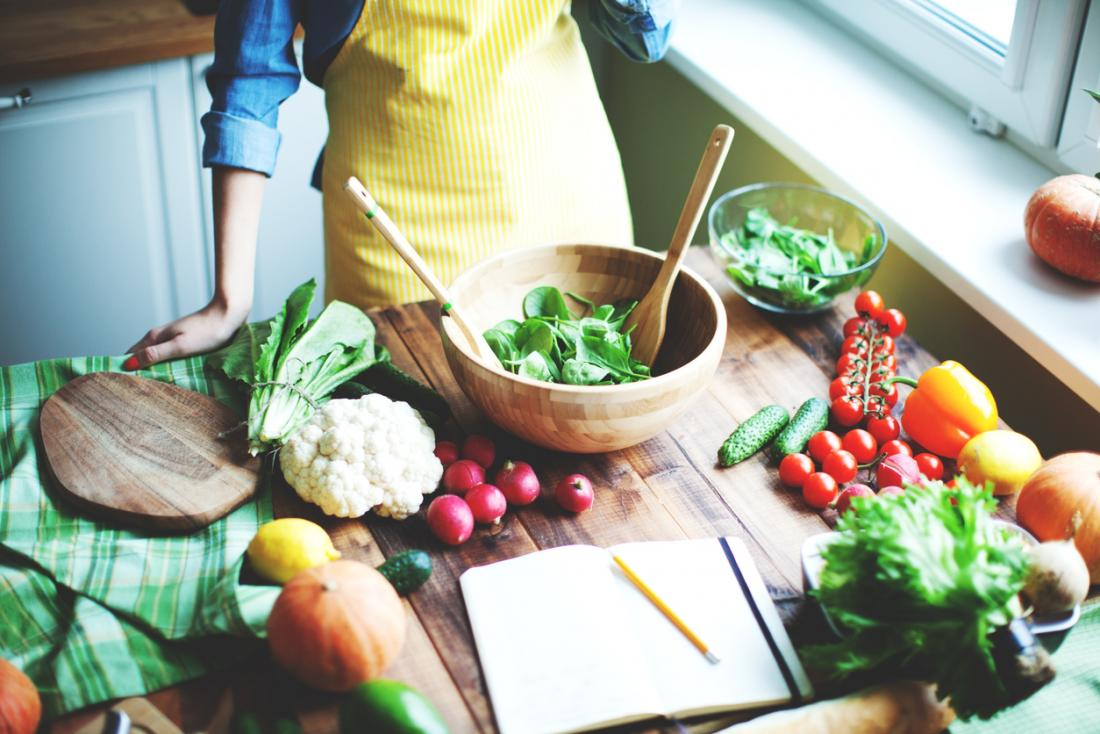 Người phụ nữ làm salad trong nhà bếp trên bàn gỗ với cuốn sách công thức. Thành phần bao gồm hạt tiêu, cà chua, củ cải, rau bina, súp lơ và các loại rau khác.