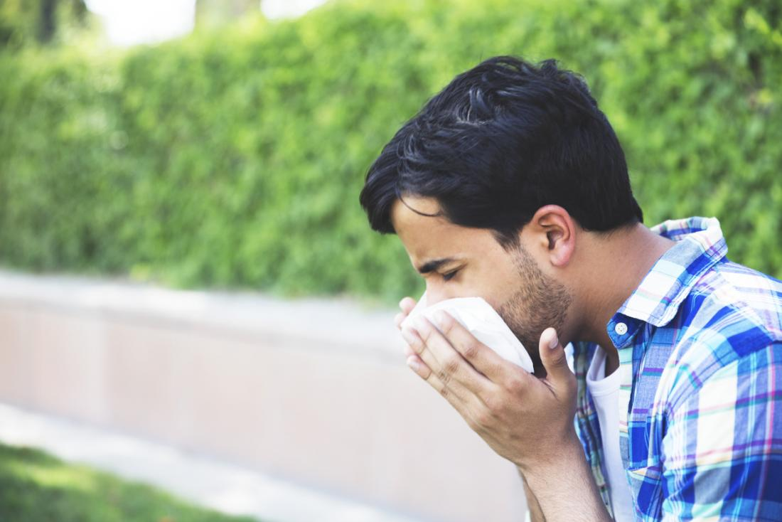 Man sitting outside in park, sneezing and blowing his nose.
