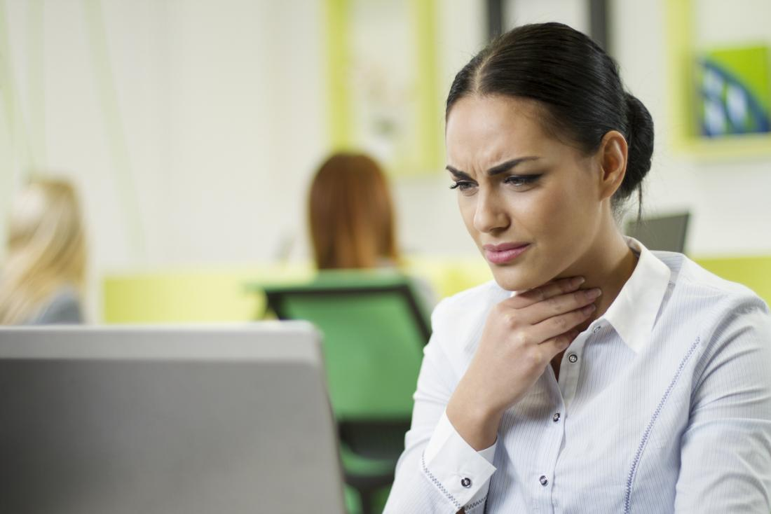 Woman at desk in office holding her throat with a pained expression.