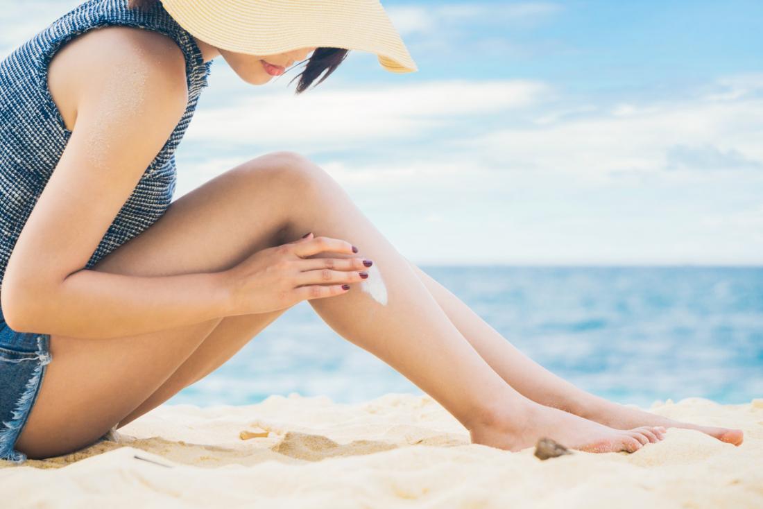 Lady on a beach applying sunscreen