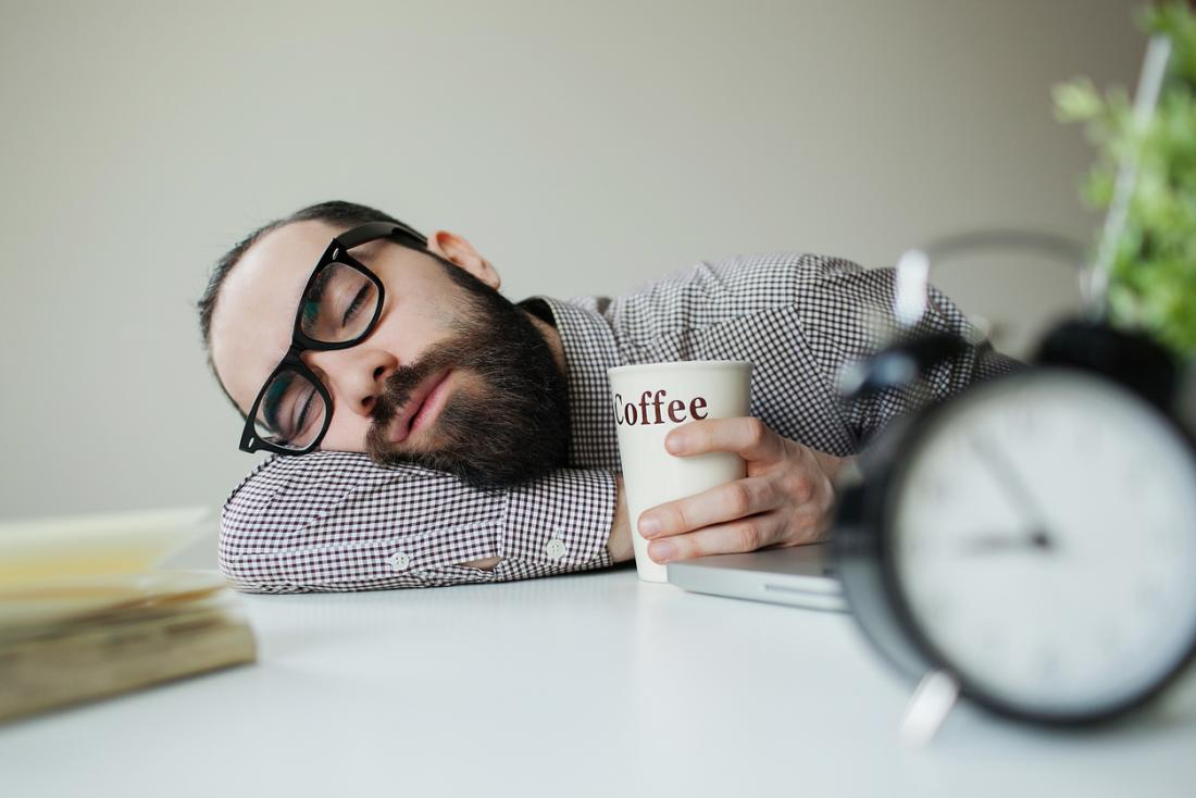 man with glasses asleep on a desk