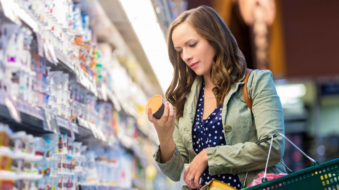 그녀의 설탕 다이어트와 일치하는 제품을 찾고 슈퍼마켓에서 쇼핑하는 여자.