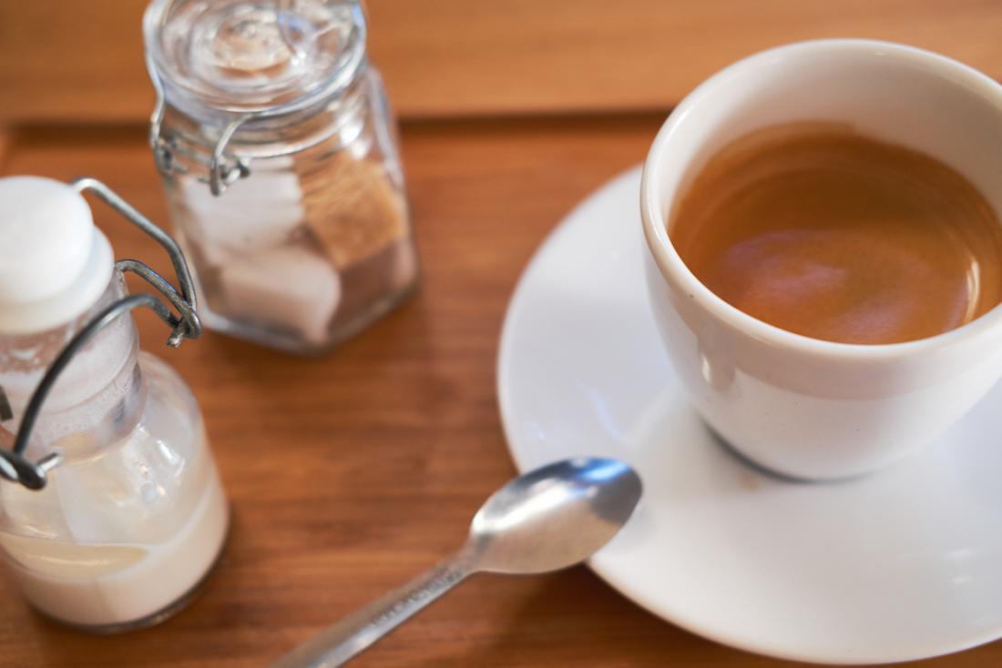 Tách cà phê với sữa và khối đường.