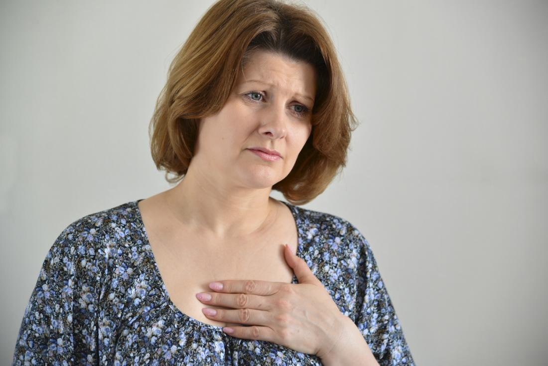 Woman holding her sternum because of pain.