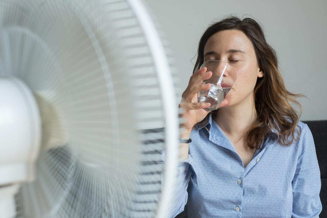 young woman sipping water in front of a fan