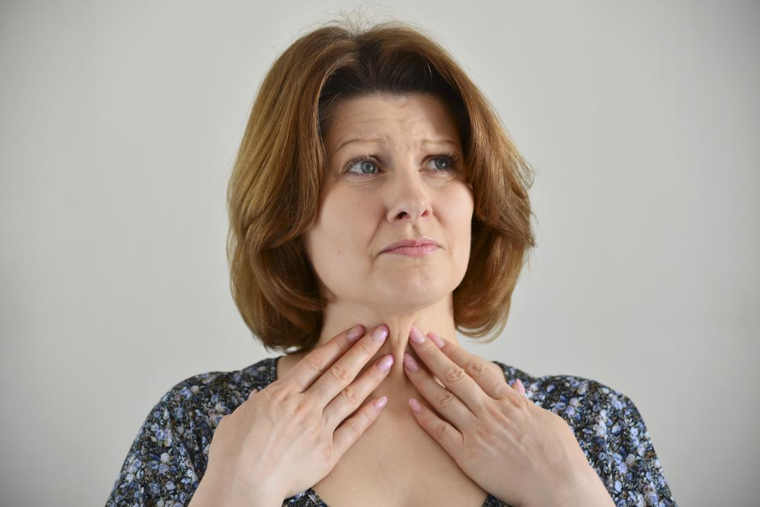 woman touching her throat with both hands