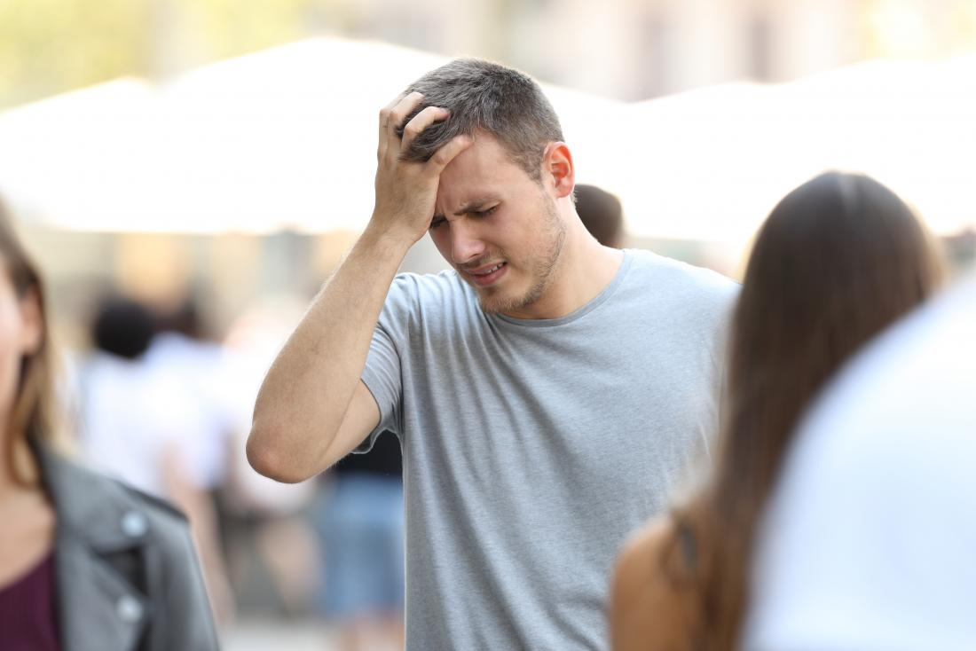 Dizzy and stressed man with headache or migraine in public place, holding his forehead in pain.