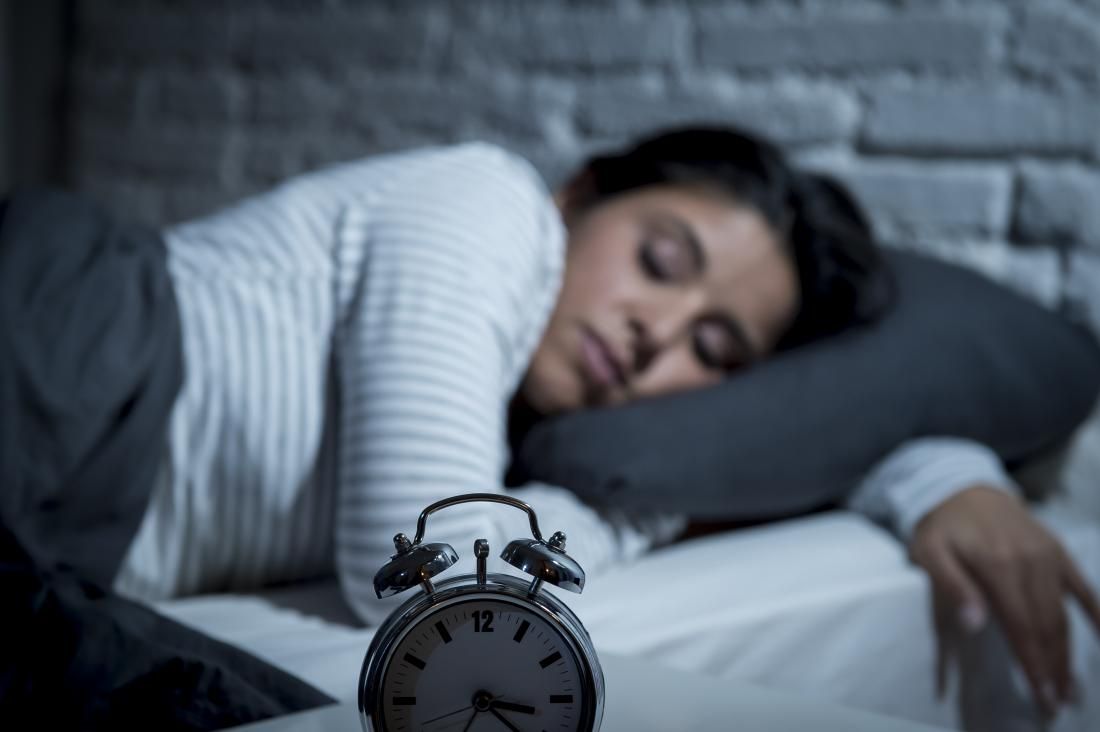 Sleeping woman in bed with alarm clock in foreground.