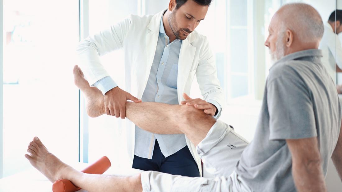 senior man receiving physio on knee
