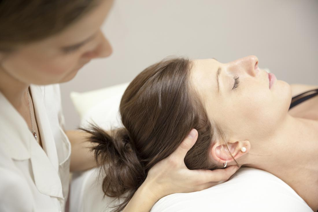 Chiropractor adjusting patient's head and neck on bed.