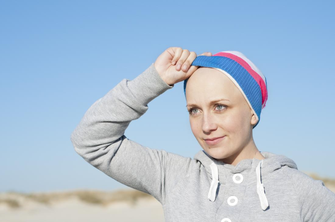 Bald woman with alopecia outside with hat on.