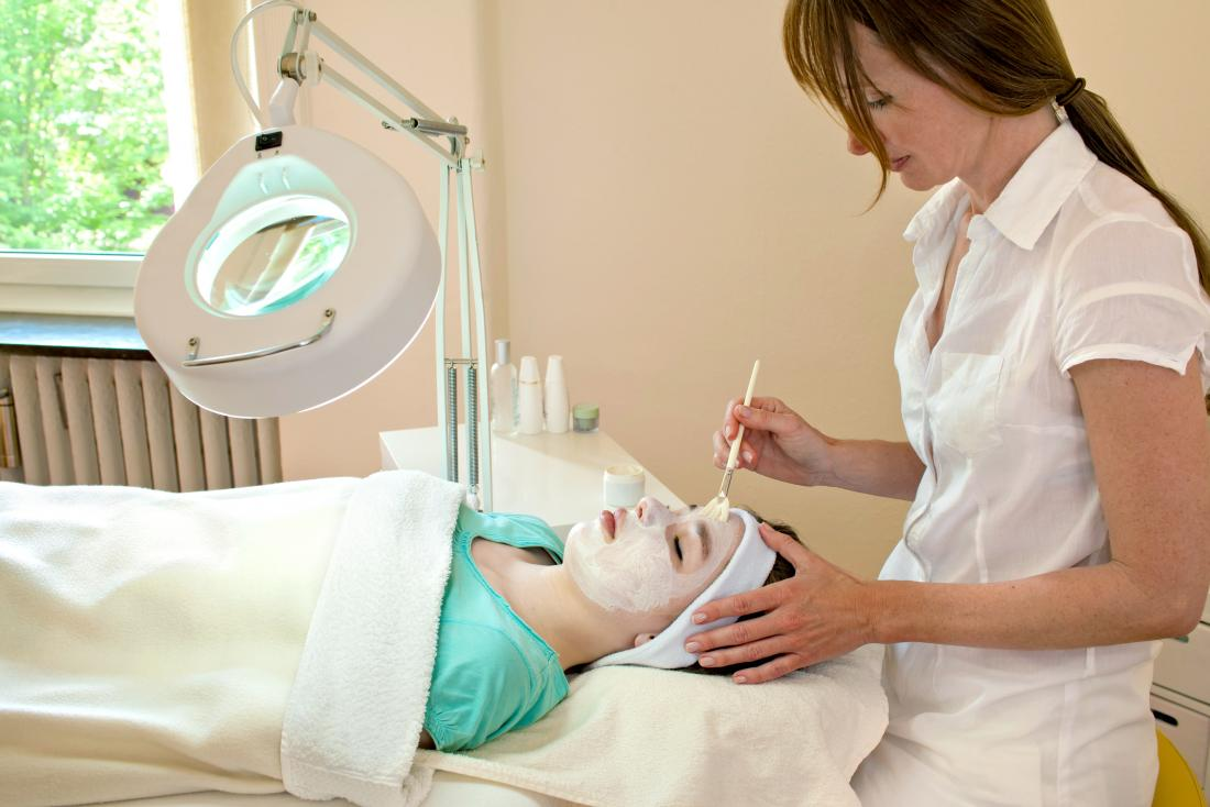 woman receiving chemical facial peel at beauty clinic.