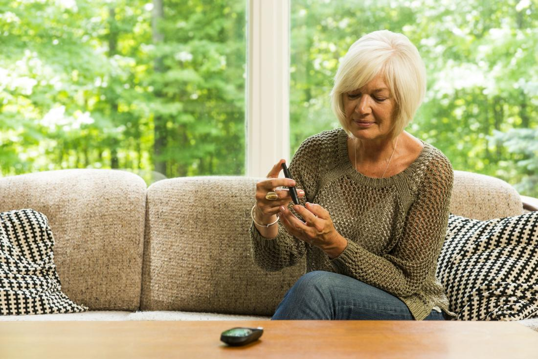 mature woman checking her blood sugar levels
