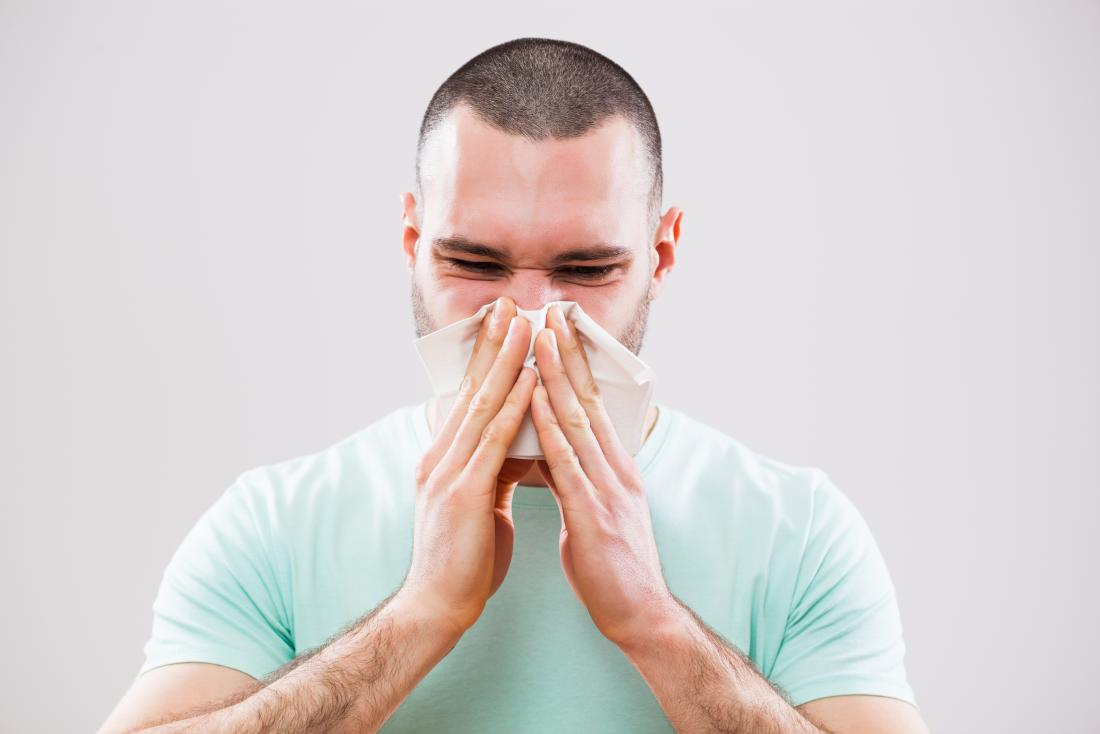 Man blowing his nose into tissue because of cold infection or sinusitis.