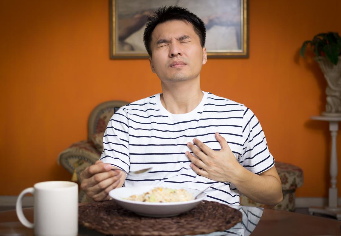 Man suffering from heartburn which may cause pain under left breast