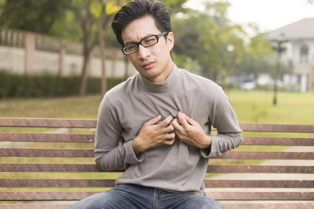 thanh niên bị đau ngực ngồi trên băng ghế trong công viên