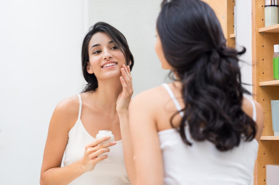 woman applying moisturizer to her oily skin
