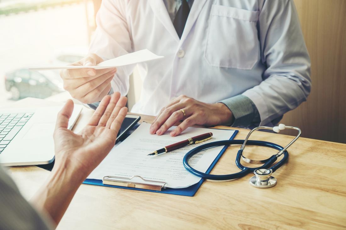 Doctor handing prescription over desk to patient.