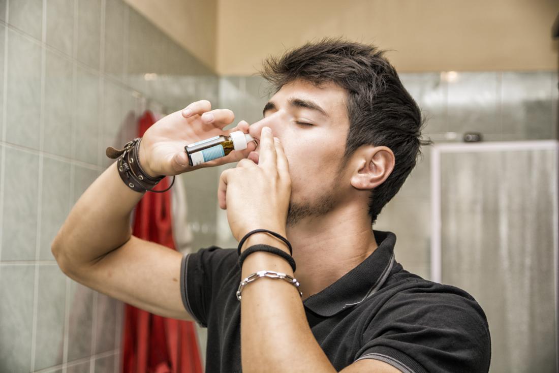 Man using nasal spray in bathroom.
