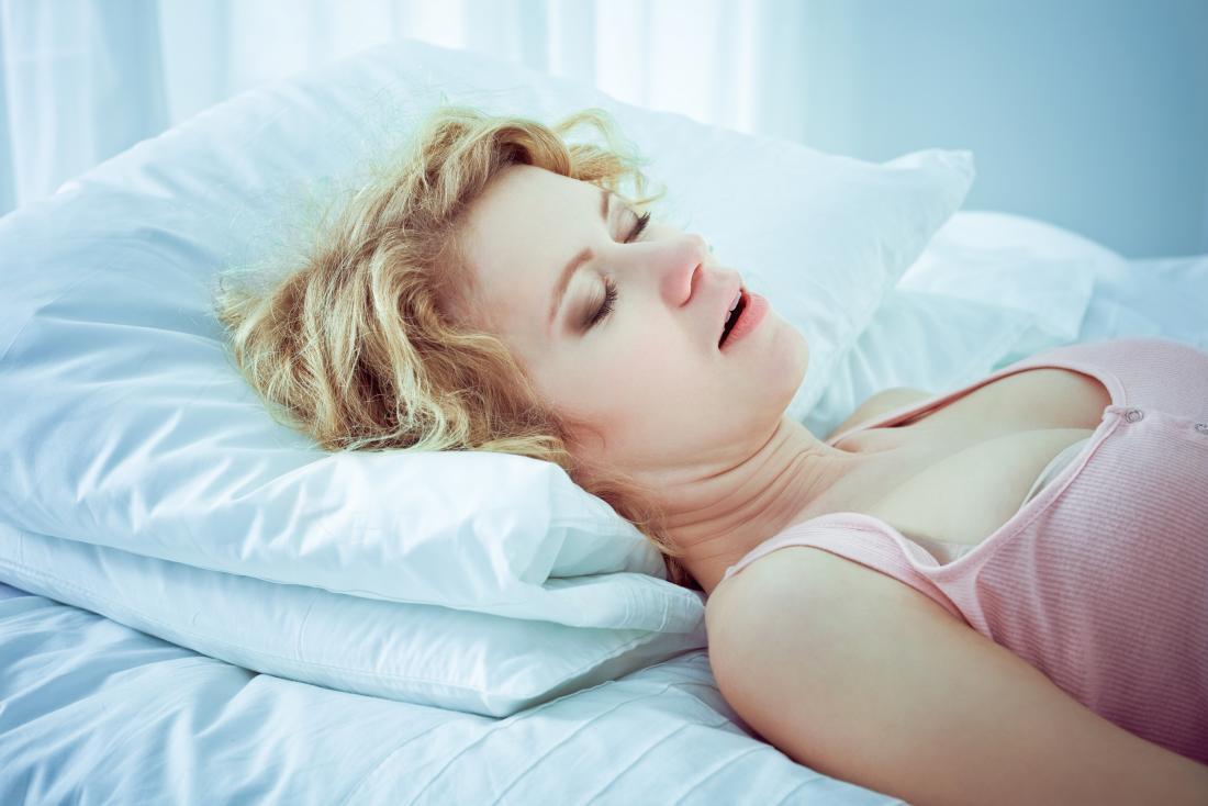 Женщина пытается храпеть домашние средства во время сна на кровати.