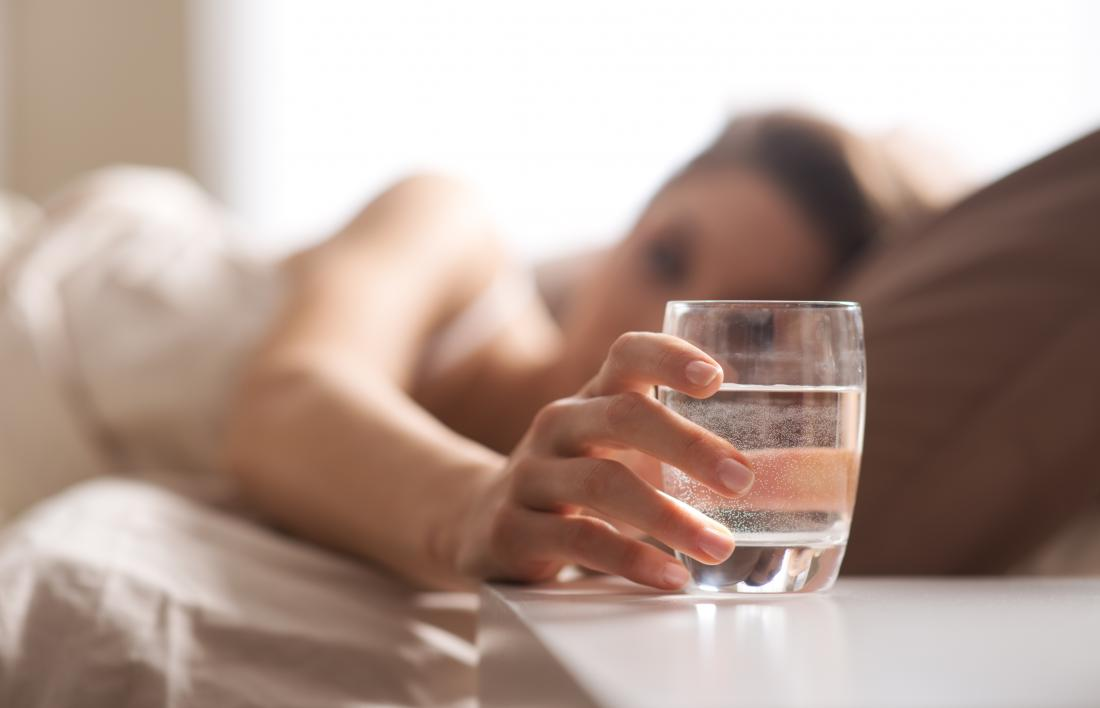 40db1518d04 Woman in bed reaching for glass of water to drink before going to sleep.