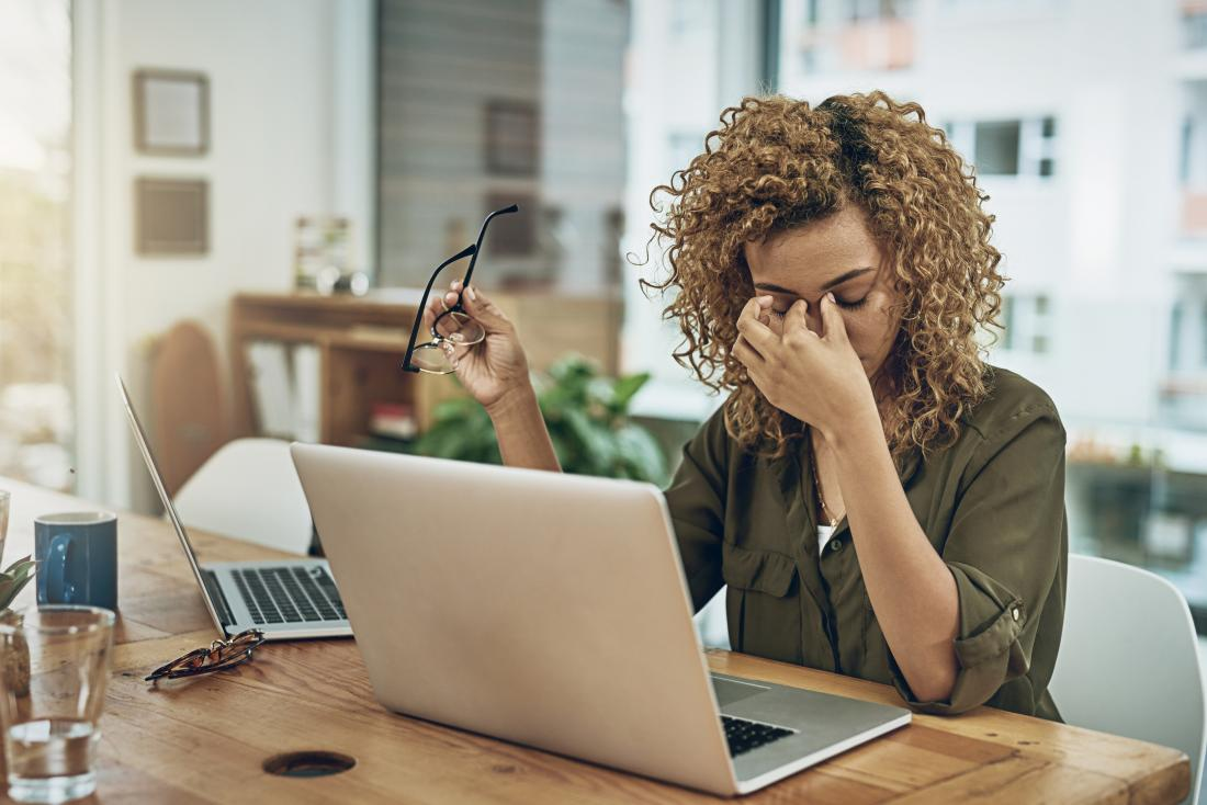 Stressed woman working in home office with two laptops rubbing bridge of nose because of tension headache.