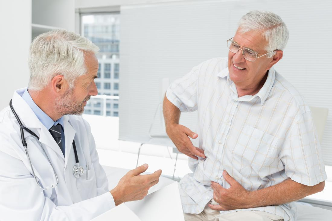 Older man at doctors sitting on bed pointing to side of stomach in pain.